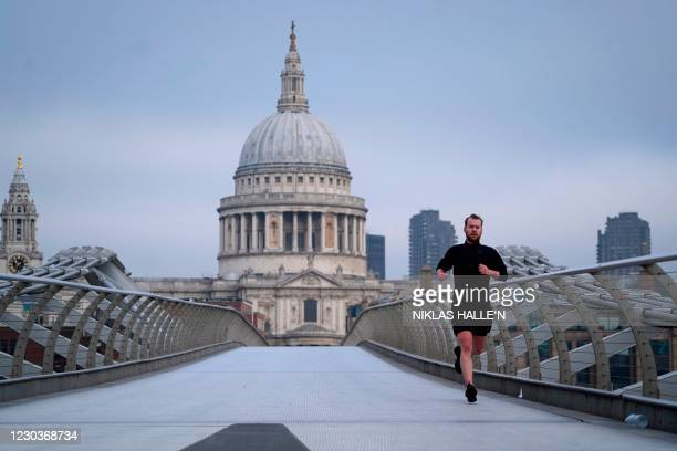 Jogger runs across the Millennium Bridge across the River Thames with St Paul's Cathedral in the background in London on December 31, 2020 on the day...