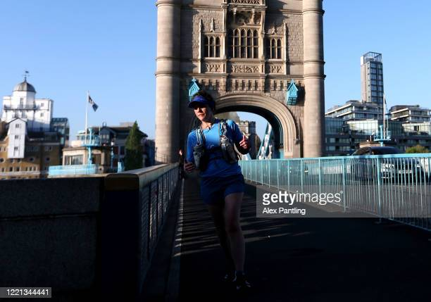 A jogger runs across Tower Bridge on April 26 2020 in London England The 40th London Marathon was due to take place today with thousands of runners...