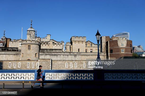 A jogger runs across Tower Bridge with the Tower of London in the background on April 26 2020 in London England The 40th London Marathon was due to...