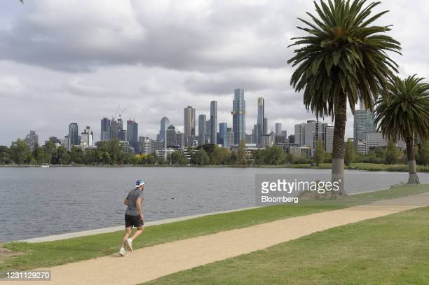 Jogger runs along Albert Park lake at the start of a five day lockdown in Melbourne, Australia, on Saturday, Feb. 13, 2021. The renewed restrictions...
