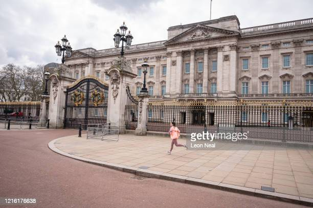 A jogger runs along the deserted pavements around Buckingham Palace on April 01 2020 in London United Kingdom The Coronavirus pandemic has spread to...