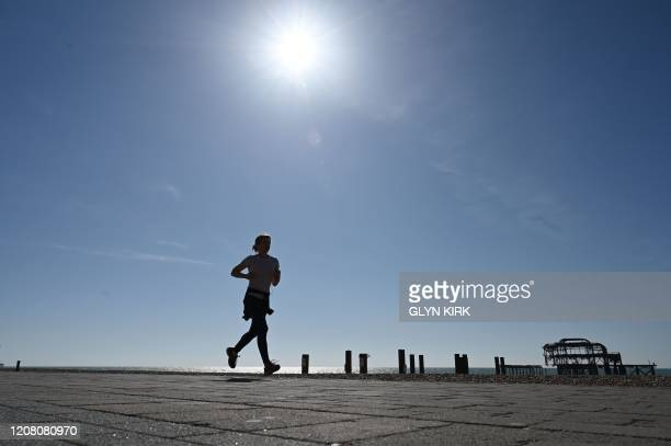 Jogger runs along the sea front in front of the dilapidated West Pier in Brighton, southern England on March 24, 2020 after Britain ordered a...