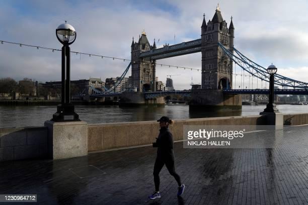 Jogger runs along the Thames river embankment near the Tower Bridge in central London on February 4 during the third national coronavirus lockdown. -...