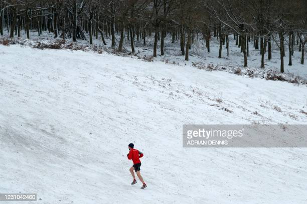 Jogger runs in the snow in Knole Park, near Sevenoaks, south of London, on February 8, 2021. - Cold weather swept across northern Europe bring snow...