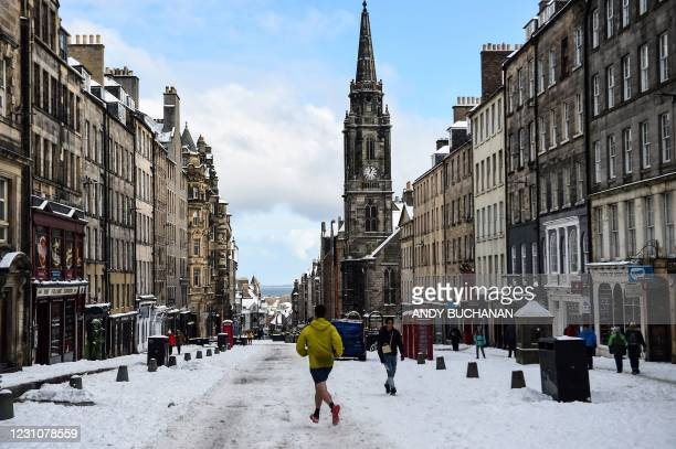 Jogger runs in the snow on the Royal Mile in Edinburgh on February 10, 2021. - Cold weather swept across northern Europe bring snow and ice.