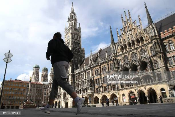 A jogger runs over the empty Marienplatz with the Townhall of Munich during the coronavirus crisis on March 31 2020 in Munich Germany Public life in...