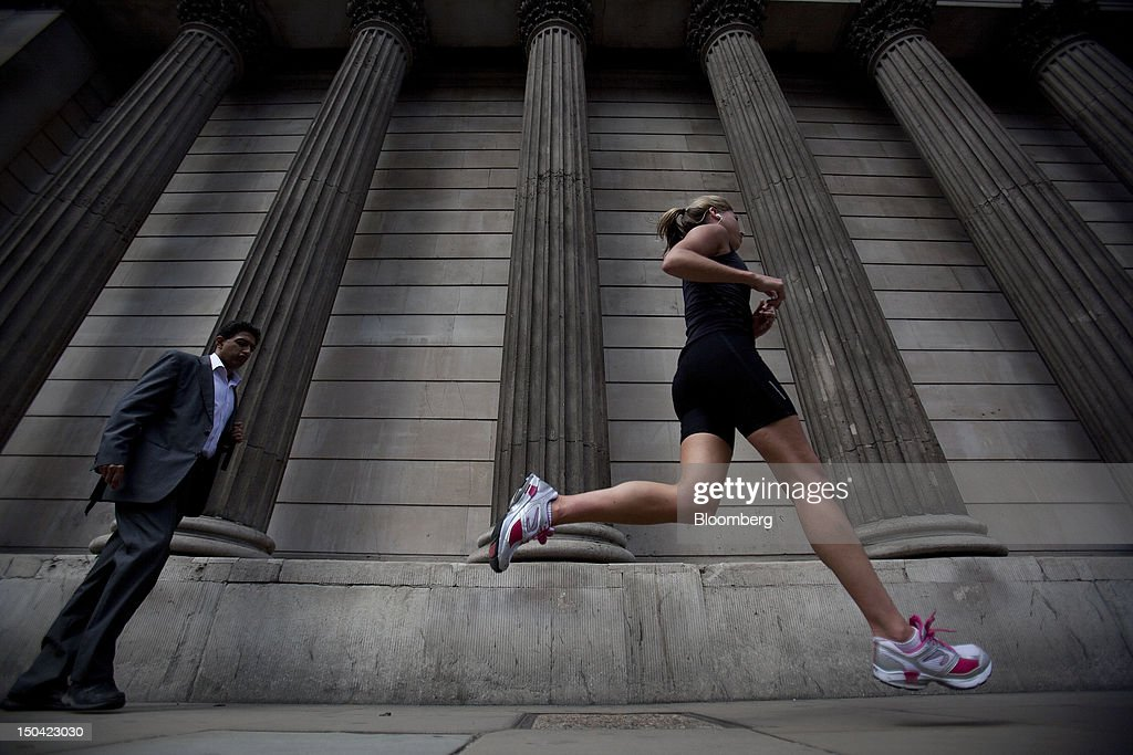 A jogger runs past a businessman as he walks past the Bank of England in London, U.K., on Friday, Aug. 17, 2012. Banks, insurers and other financial-services firms may eliminate a total of about 3,000 jobs across greater London as companies in the New York region add 9,000, according to U.K.-based researcher Oxford Economics Ltd. Photographer: Simon Dawson/Bloomberg via Getty Images