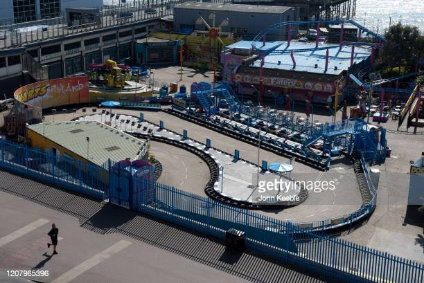 A jogger runs past a closed leisure park Adventure Island due to the Coronavirus pandemic on Mother's day March 22 2020 in Southend on Sea England...
