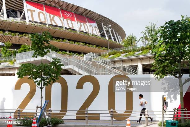 Jogger runs past a large Tokyo 2020 sign around the National Olympic stadium, Gaiemmae. The Tokyo Olympic Organizing committee are planning to open...