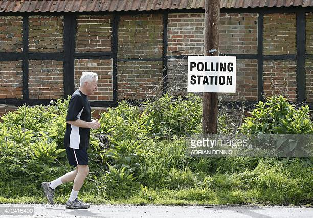 A jogger runs past a polling station sign for Mattingley church hall in southern England on May 7 as Britain holds a general election Polls opened...