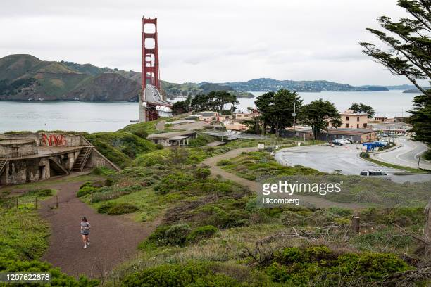 Jogger runs past an empty parking lot and the Golden Gate Bridge in the Golden Gate National Recreation Area in San Francisco, California, U.S., on...