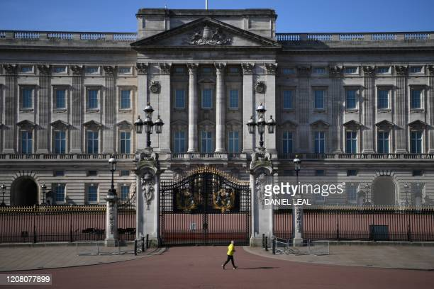 A jogger runs past Buckingham Palace in central London on the morning on March 24 2020 after Britain ordered a lockdown to slow the spread of the...