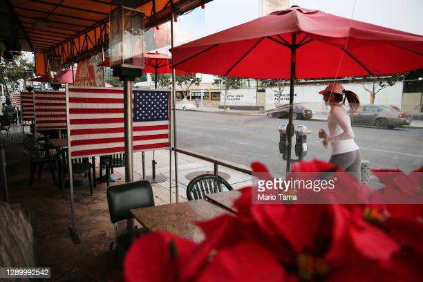 Jogger runs past closed outdoor restaurant seating decorated with American flags on the first day of new stay-at-home orders on December 7, 2020 in...