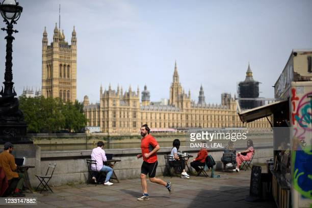 Jogger runs past patrons sitting at outdoor tables of a cafe on the embankment of the River Thames opposite the Houses of Parliament, on a sunny day...