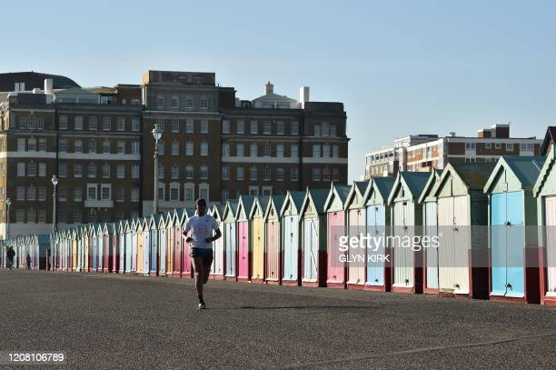 Jogger runs past the beach huts on the sea front at Hove, Brighton, southern England, on March 24, 2020 after Britain ordered a lockdown to slow the...