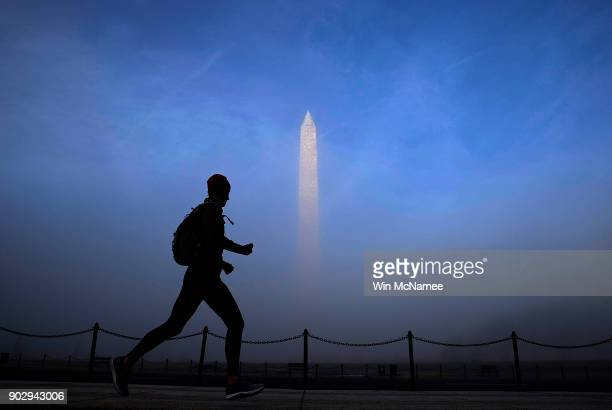 A jogger runs past the Washington Monument as thick fog enveloped the nation's capital January 9 2018 in Washington DC With subzero temperatures...