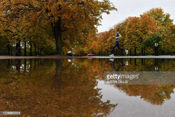 Jogger runs past trees reflected in a puddle after rainfall in Greenwich Park, south-east London on October 3, 2020. - Heavy rain is lashing parts of...