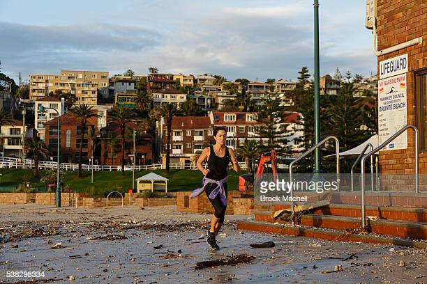 A jogger runs throug debris at Bronte Beach on June 6 2016 in Sydney Australia Torrential rain over the weekend saw streets and homes flooded while...