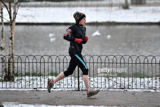 Jogger runs through a snow-covered Green Park in central London on February 9, 2021. - Cold weather swept across northern Europe bring snow and ice.