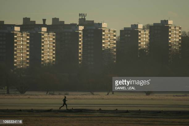 TOPSHOT A jogger runs through Richmond park at sunrise on a winters morning in south west London on February 3 2019 England saw the coldest night of...