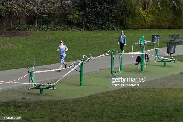 A jogger runs to exercise past closedoff gym equipment due to the ongoing Covid19 pandemic in Queen's Park Glasgow on March 24 2020 after Britain...