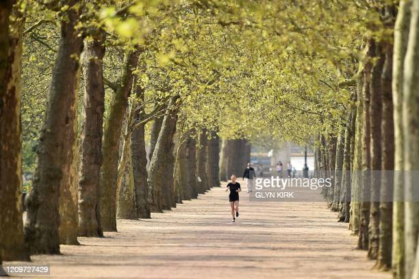 A jogger runs to take their daily exercise allowance along a treelined avenue adjacent to The Mall road in central London on April 12 as life in...