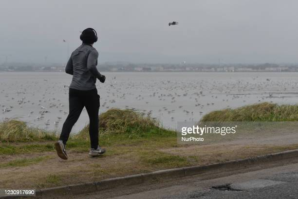 Jogger seen near The Great South Wall in Dublin during Level 5 Covid-19 lockdown. On Monday, 1 February in Dublin, Ireland.