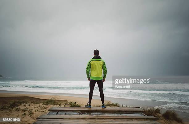 Jogger standing at the beach on a stormy day, Valdovino, Galicia, Spain.