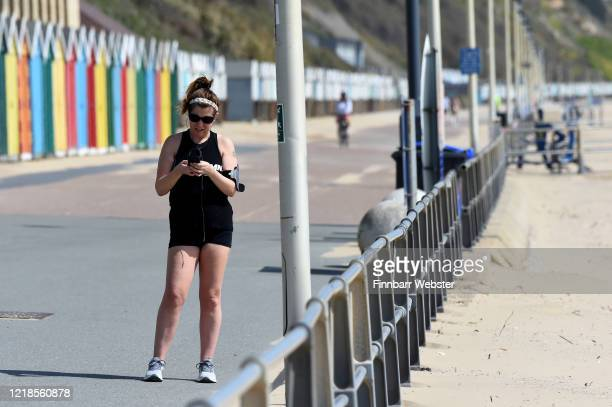 A jogger stops to check her phone on the promenade at Boscombe beach on April 13 2020 in Bournemouth United Kingdom The Coronavirus pandemic has...