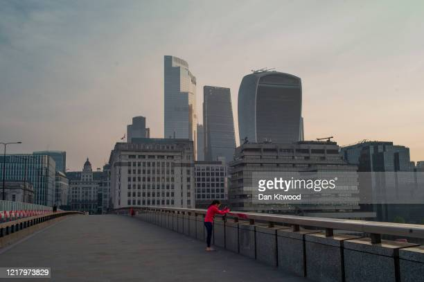 A jogger stops to take a photograph at sunrise on an otherwise empty London Bridge usually thronged with city workers on April 10 2020 in London...