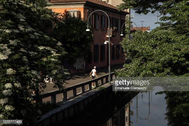 A jogger stretches out on May 04 2020 in Milan Italy Starting today more than 4 millions of Italians will get back to work as manufacturers...