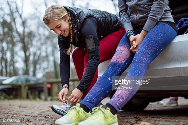 jogger tying shoelace by friend on car trunk - leggings stock pictures, royalty-free photos & images