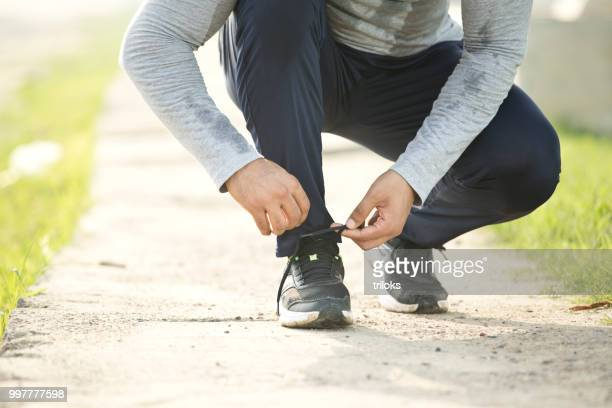 low section man tying shoelace