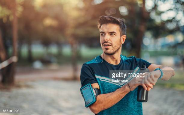 jogger using a smart watch - jogging stock pictures, royalty-free photos & images