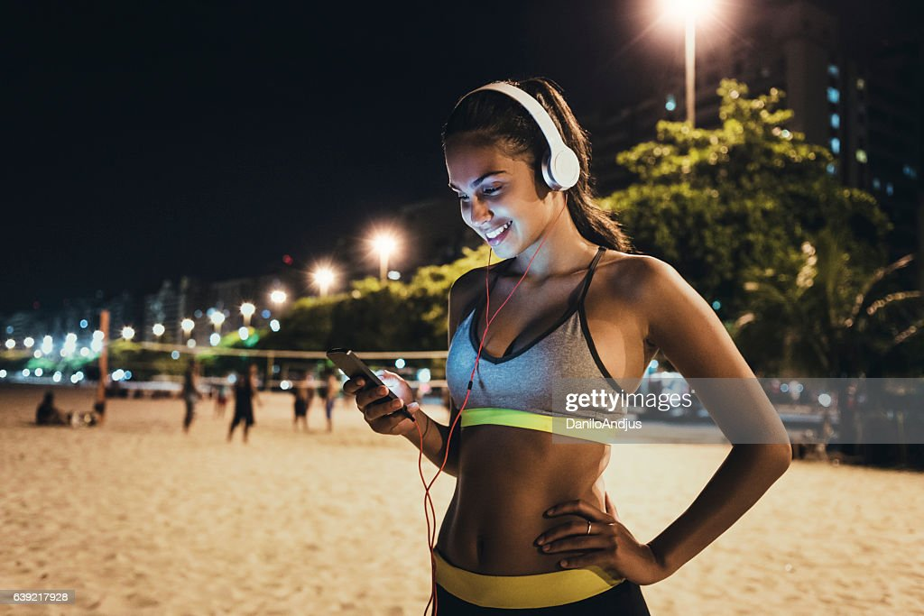 jogger using her smartphone and resting : Stock Photo