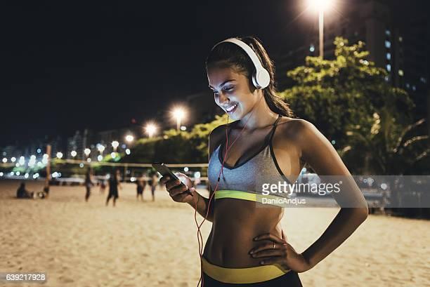 jogger using her smartphone and resting - correndo - fotografias e filmes do acervo