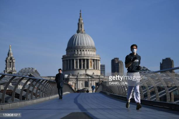 A jogger wears a mask as he runs along Millenium Bridge in London on the morning on March 24 2020 after Britain ordered a lockdown to slow the spread...