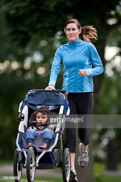 Jogger With Baby Jogger Running On a Paved Trail.