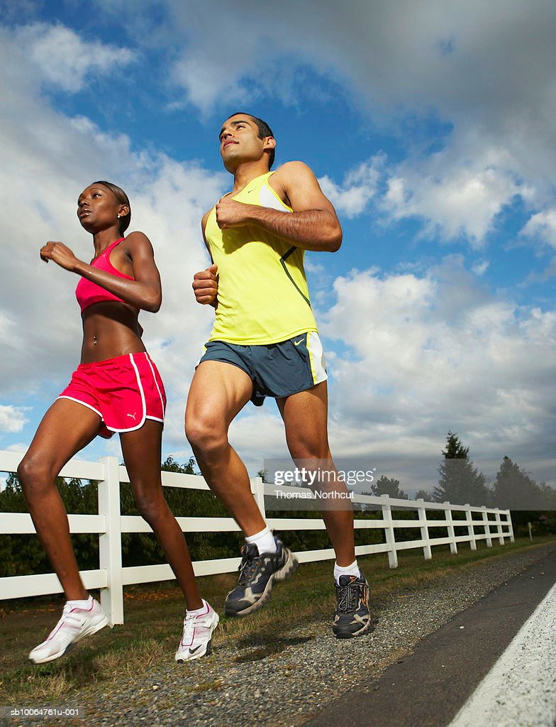 Joggers by road, low angle view : Stock Photo