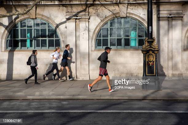 Joggers carry out their daily exercise along the Embankment Bridge during the Covid-19 lockdown in London.