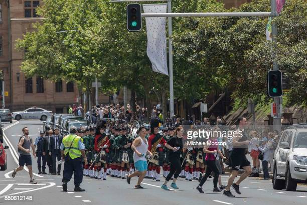 Joggers cross the road as pipers from Scott's College accompany the funeral cortege down College Street after the funeral service for AC/DC cofounder...