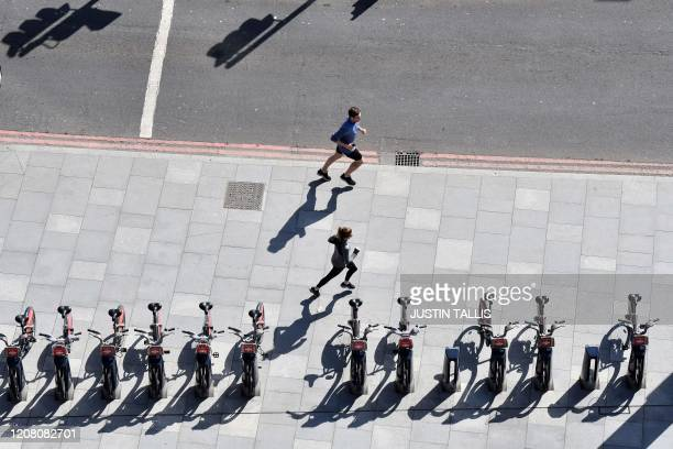 Joggers keep their distance as they run down an empty street in south London on March 24 2020 after Britain ordered a lockdown to slow the spread of...