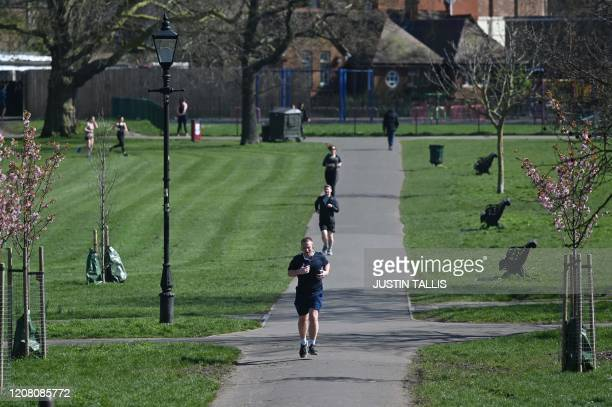 Joggers keep their distance from each other as they exercise on Clapham Common in south London on March 24 2020 after Britain's government ordered a...