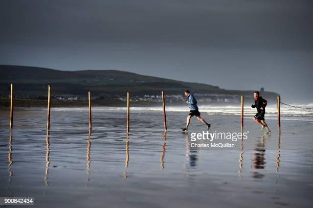 Joggers make their way across Portstewart strand after Storm Eleanor recorded winds of up to 90mph on January 3 2018 in Portrush Northern Ireland The...