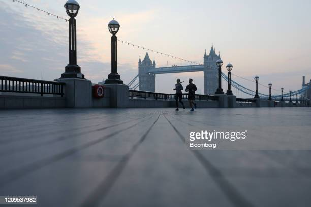 Joggers pass in view of Tower Bridge in London UK on Thursday April 9 2020 UK Prime Minister Boris Johnson spent a third night in the critical care...