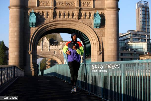 Joggers run across Tower Bridge on April 26 2020 in London England The 40th London Marathon was due to take place today with thousands of runners due...
