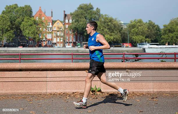 Joggers run along the river Thames by Battersea Park in south west London as temperatures soar on September 14 2016 / AFP / JUSTIN TALLIS