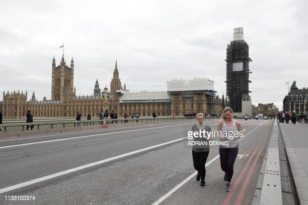 Joggers run along Westminster Bridge near the Houses of Parliament in Westminster, central London on March 27, 2019. - British MPs are set to hold a...