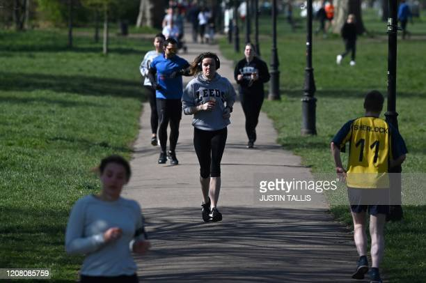 Joggers run as they exercise on Clapham Common in south London on March 24 2020 after Britain's government ordered a lockdown to slow the spread of...