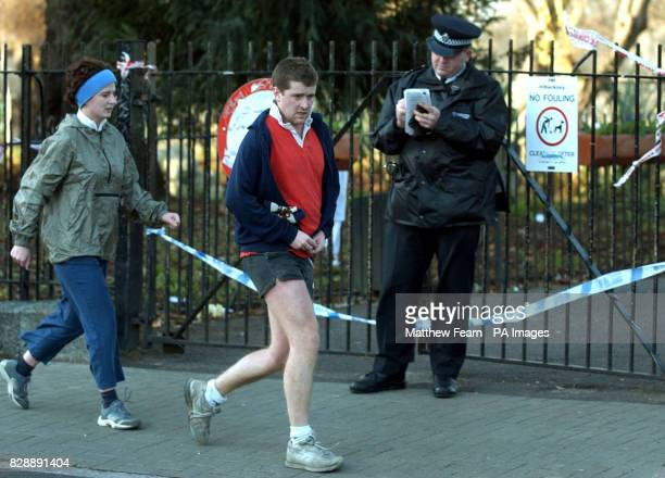 Joggers run past a police officer outside a sealedoff Clissold Park in Stoke Newington east London after a jogger was attacked yesterday Detectives...